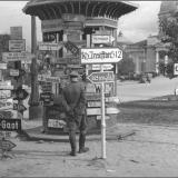 Немецкий офицер рассматривает дорожные указатели в оккупированном Курске. На дальнем плане здание Знаменского кафедрального собо